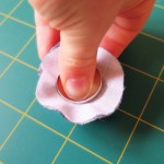 pushing the button top into the mould to make a fabric covered button
